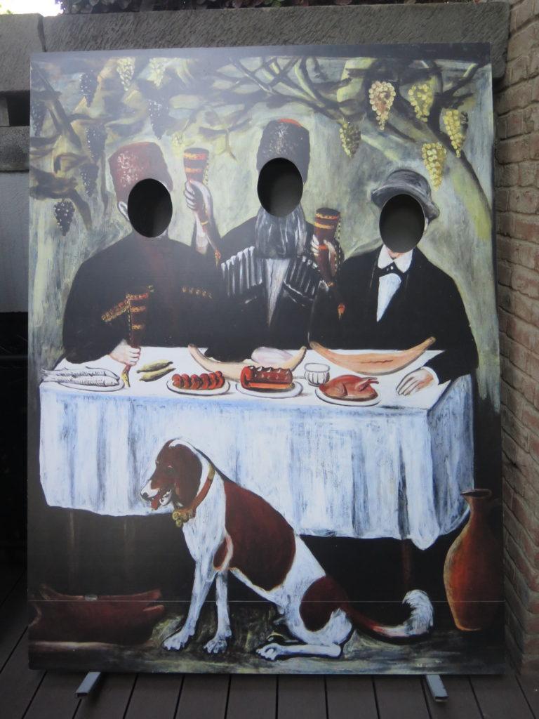 Udenfor en Easy Wine restaurant i Tbilisi kan man blive fotograferet på Pirosmani maleriet Feast in a Grape Gazebo