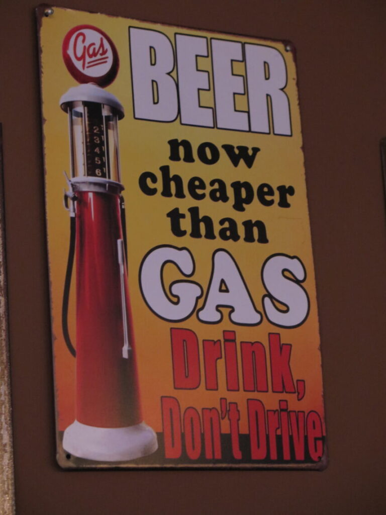 En af de sjove ølplakater: BEER now cheaper than GAS. DRINK, Don't Drive